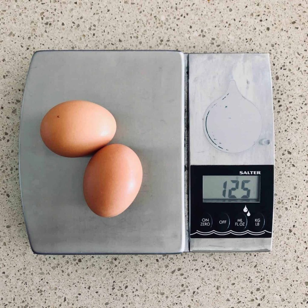 weighing eggs for butterfly cakes