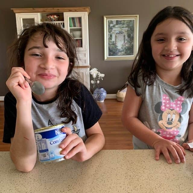 girls eating condensed milk from tin
