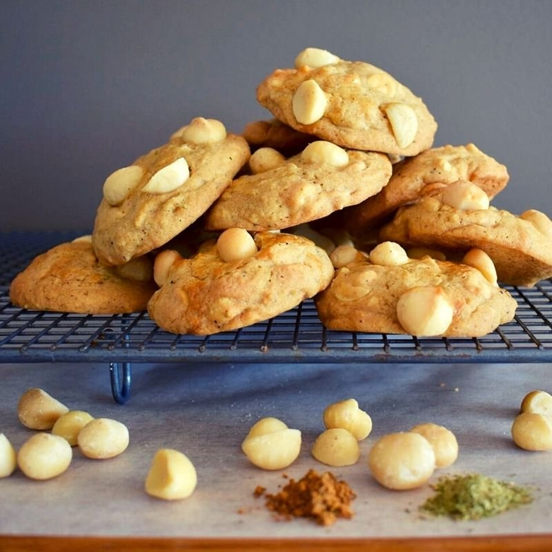 macadamia cookies on cooling tray with scattered nuts and spices