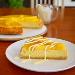 slice of baked mango cheesecake served with drizzled cream