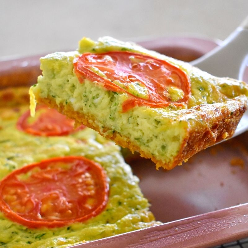 zucchini slice being lifted from tray