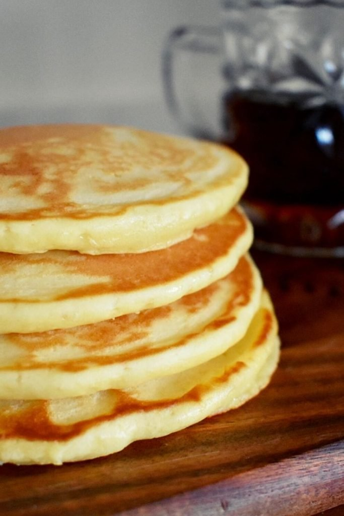 scotch pancakes with jug of maples syrup in background