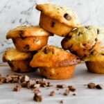 banana choc chip muffins stacked with choc chips scattered in foreground
