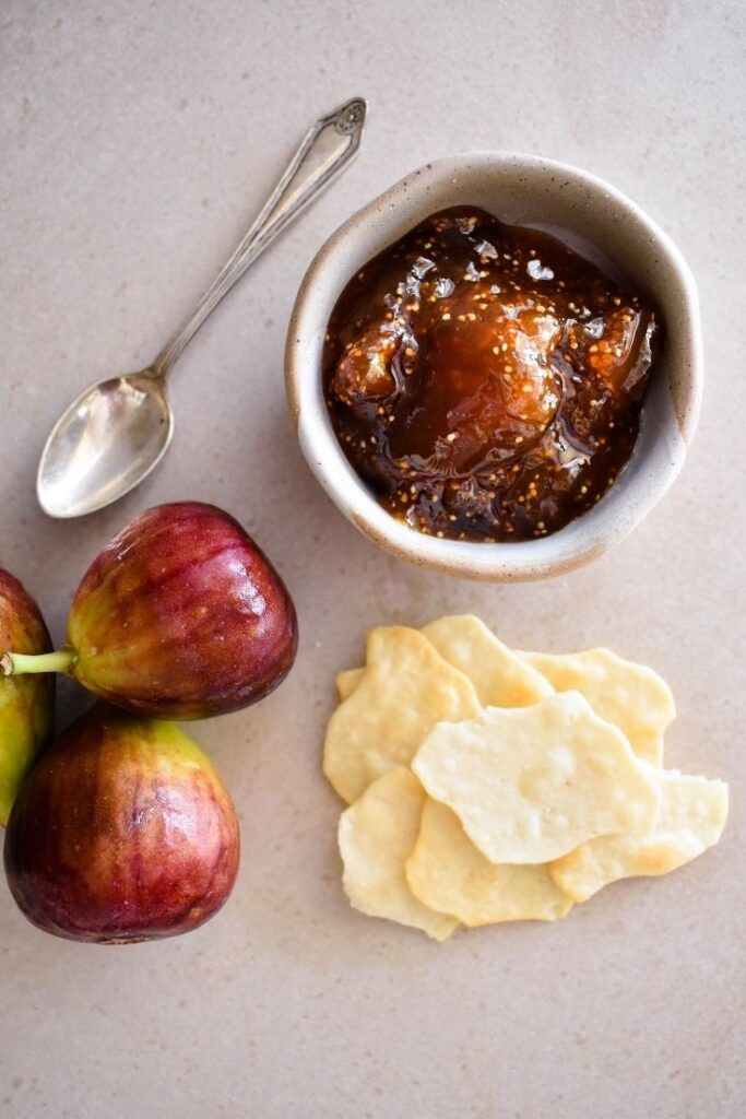 fig jam in bowl with crackers and fresh figs in display