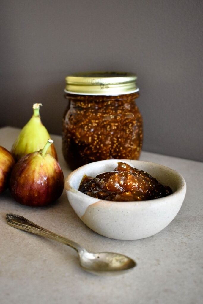 fig jam on bench with two fresh figs
